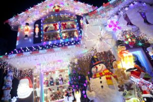 Home covered in Christmas lights with a snowman in front yard