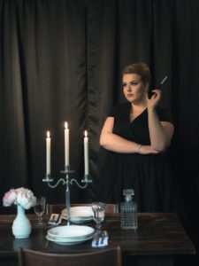 murder mystery dinner with woman standing over a table with a candle