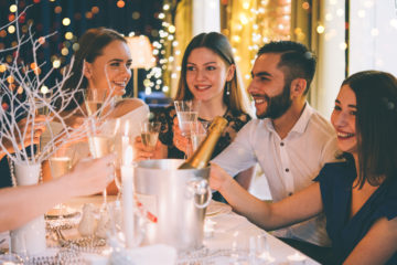 picture of people at a table drinking champagne celebrating New Years 2018