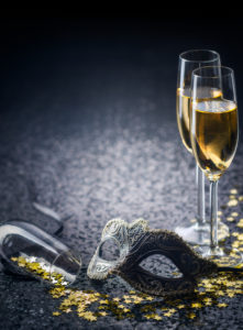 glass of champagne with a masquerade mask