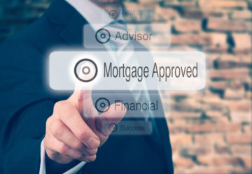 Finger pointing to a touch screen showing Mortgage Approved text