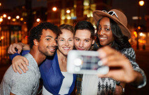 Multi-ethnic millenial group of friends taking a selfie photo with mobile phone on rooftop terrasse using flash at night time