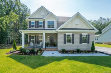 Home with front porch and sidewalk with green grass in chesterfield county
