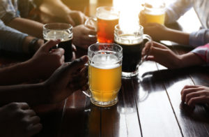 group of people drinking beer in a brewery sitting at a table