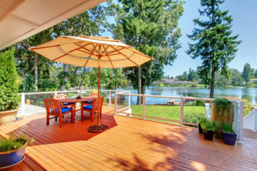 deck with chairs and umbrella looking at a lake