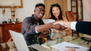 couple sitting at a desk shaking hands with a real estate agent with computer and paper on desk