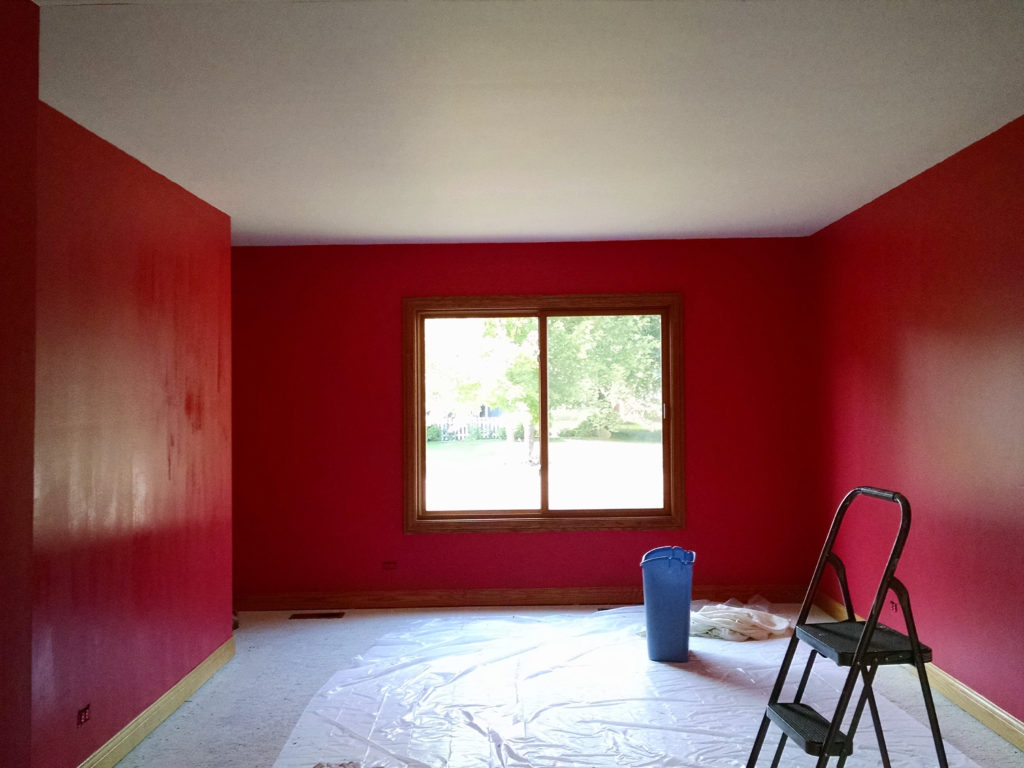 living room with bold red color with paint bucket in middle with tarp on floor