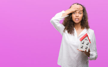 lady holding a house with face palm to the forehead because of a mistake in front of a purple background