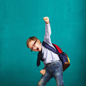 young boy with a backpack on wearing glasses giving a fist pump in air excited about school