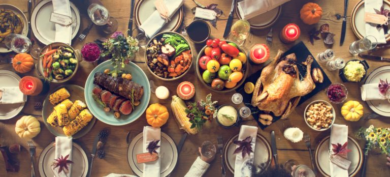 a thanksgiving dinner spread on a long table to feed a lot of people