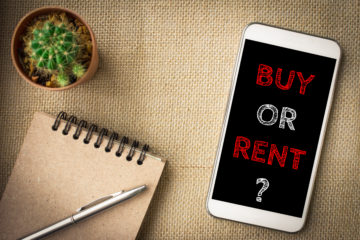 is it cheaper to own or rent a home question on a smartphone laying on a table with notepad and pen and a small plant