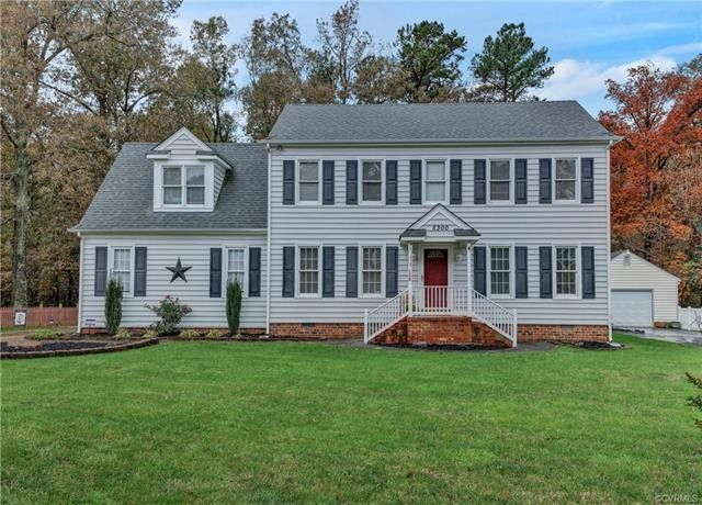 grey colonial home with red door and dark gray shutters with big front yard