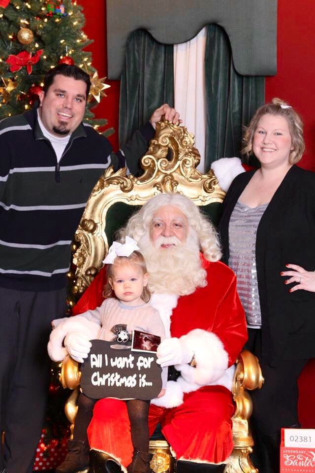family with santa announcing pregnancy with ultrasound photo
