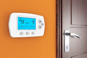 orange wall with a white programmable thermostat for heating