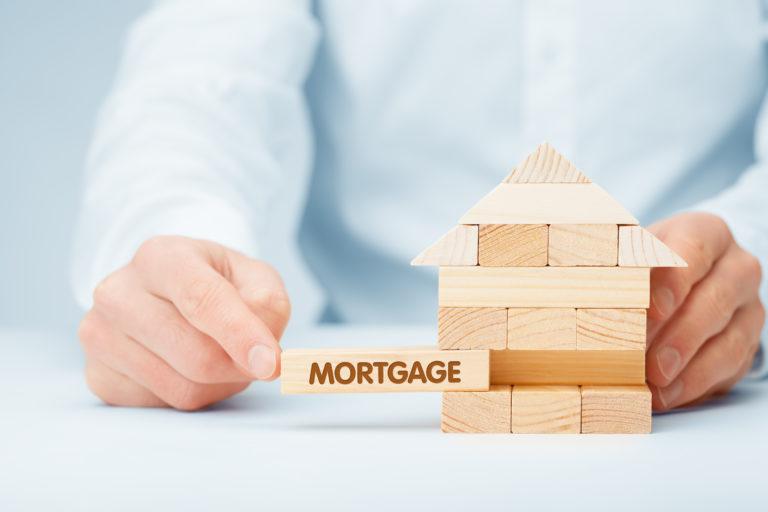 Mortgage concept. Financial agent complete wooden model of the house with last piece with text mortgage. - Image