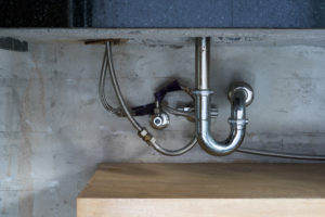 stainless steel pipes under a sink next to a gray concrete wall