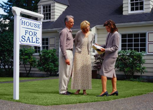 Couple with Real Estate Agent and For Sale Sign