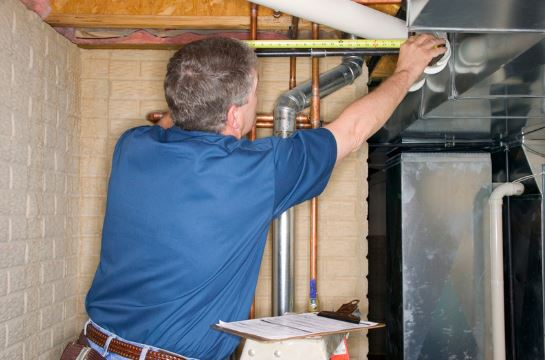 home inspector measuring pipes