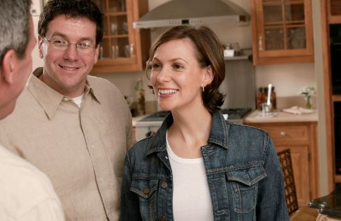 Couple talking to real estate agent in kitchen