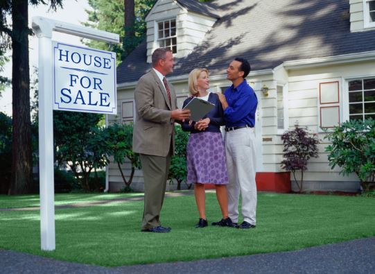 real estate agent with home sellers next to sign